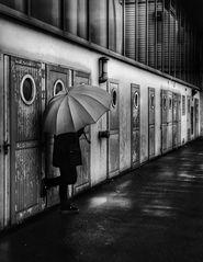 Die Frau mit dem Regenschirm wartet darauf dass sich eine Türe öffnet (59)