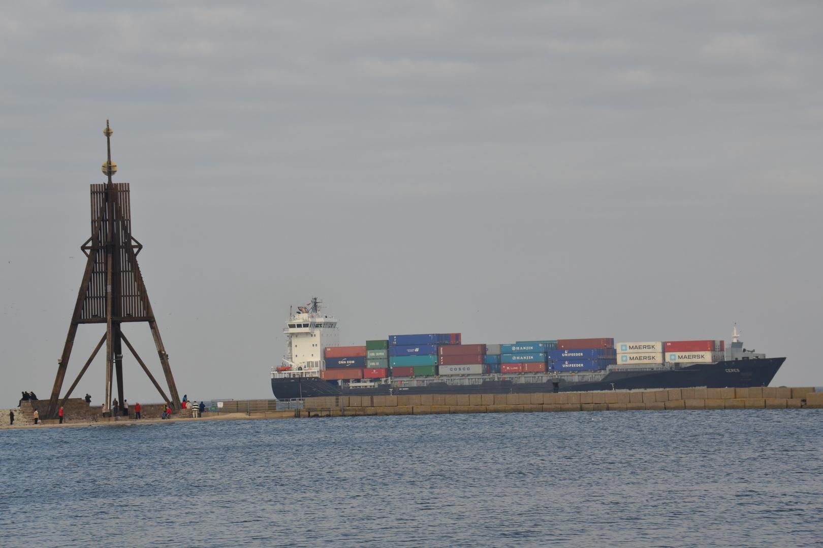 die Kugelbake in Cuxhaven mit einem Containerschiff im Hintergrund