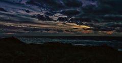 Die Sonne begibt sich hinter dunklem Wolken zur Ruhe.