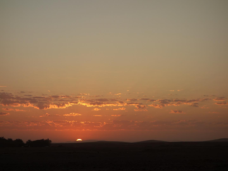 Die Sonne blinzelt ueber den Horizont