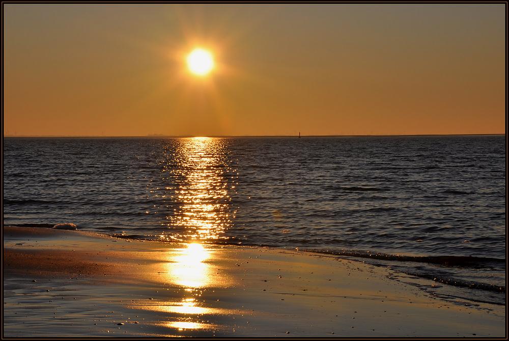 Die Sonne geht am goldenen Strand von Langeoog