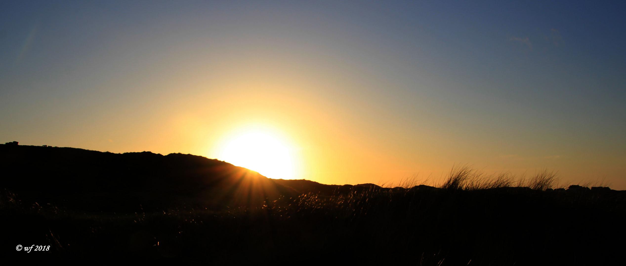 Die Sonne verschwindet hinter der Düne