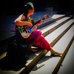 die Strassenmusikerin  unbeschwert bunt und voller Hingabe ans Leben