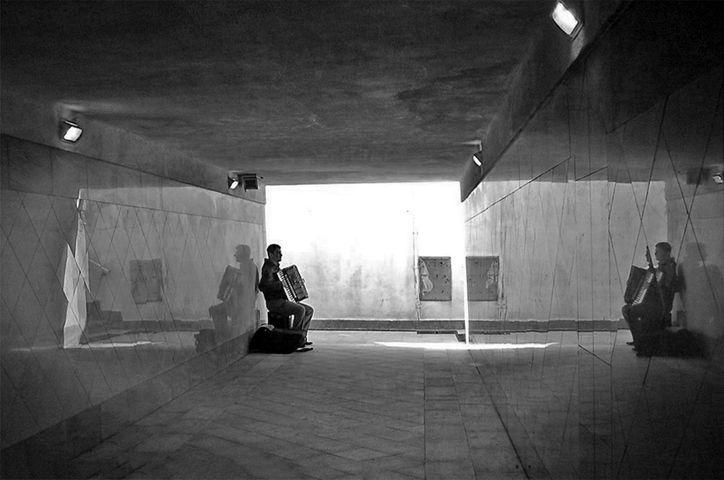 Double reflection of the accordion player in the underpass of Bordighera station