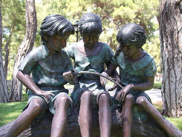 Drei Kinder auf Baumstamm
