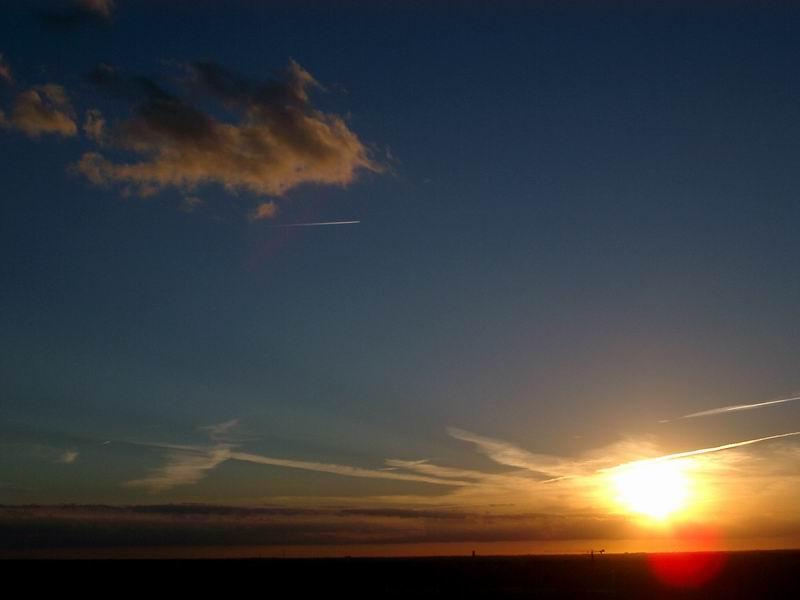 Ein Flugzeug fliegt in die Abenddämmerung