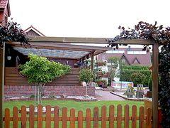 ein Garten mit überdachter Terrasse