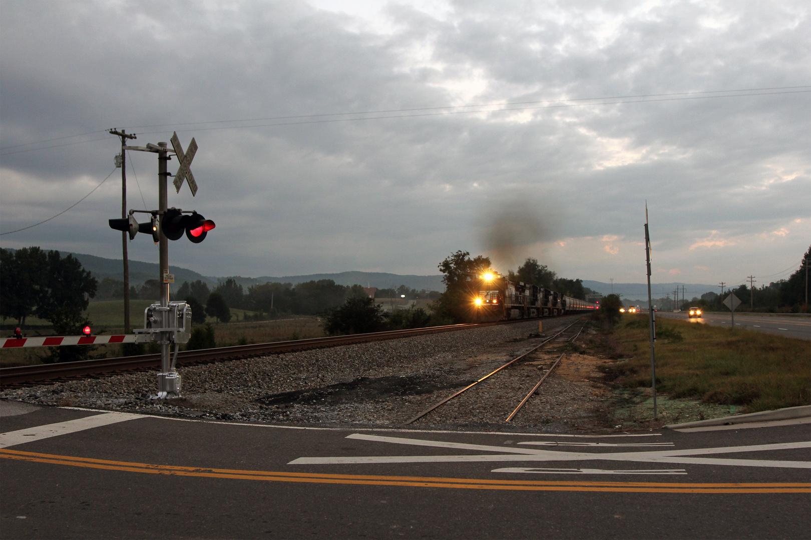 Ein Güterzug mit Getreidewagen nähert sich dem Bahnübergang mit Horn und Warnlichtern,USA