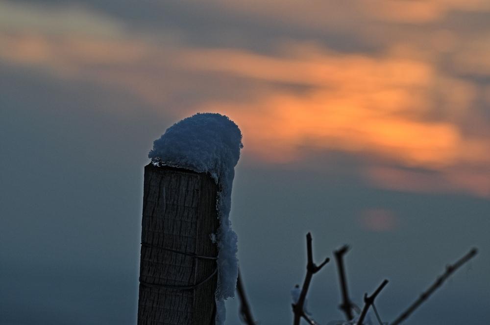 Ein Holzstecken überdeckt mit schnee und einem schönen Sonnenuntergang