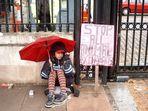 Ein Mädchen hat eine Botschaft - bei Regen in London