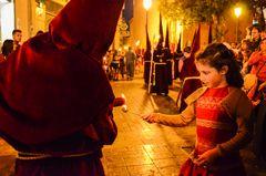 Ein Nazareno (Büßer) beträufelt den Wachsball eines kleinen Mädchens