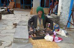 Ein Schneider vor seinem Haus