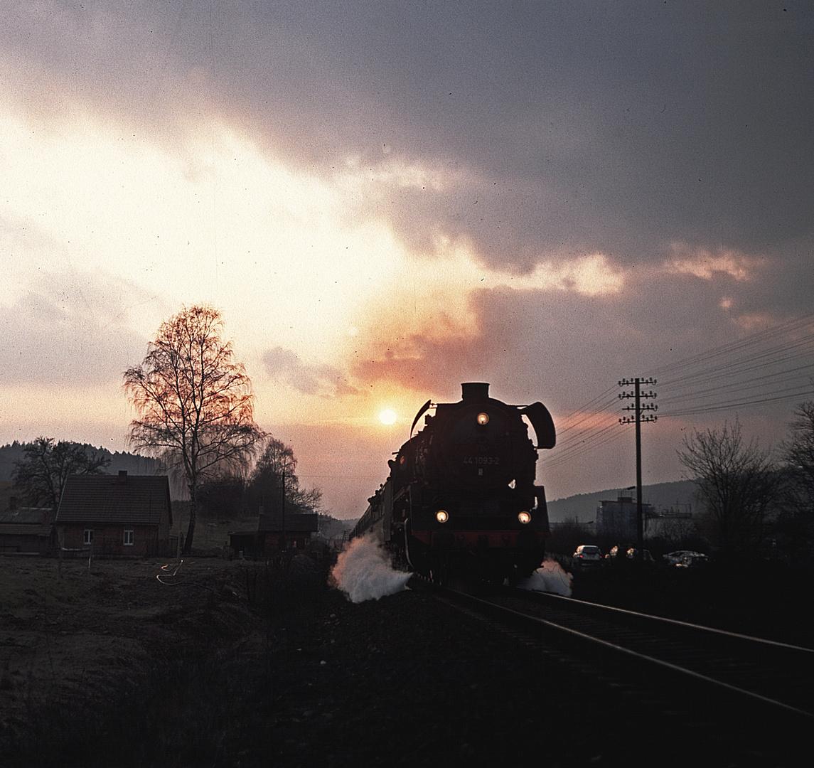 Eine Güterzugdampflok befördert einen Schnellzug