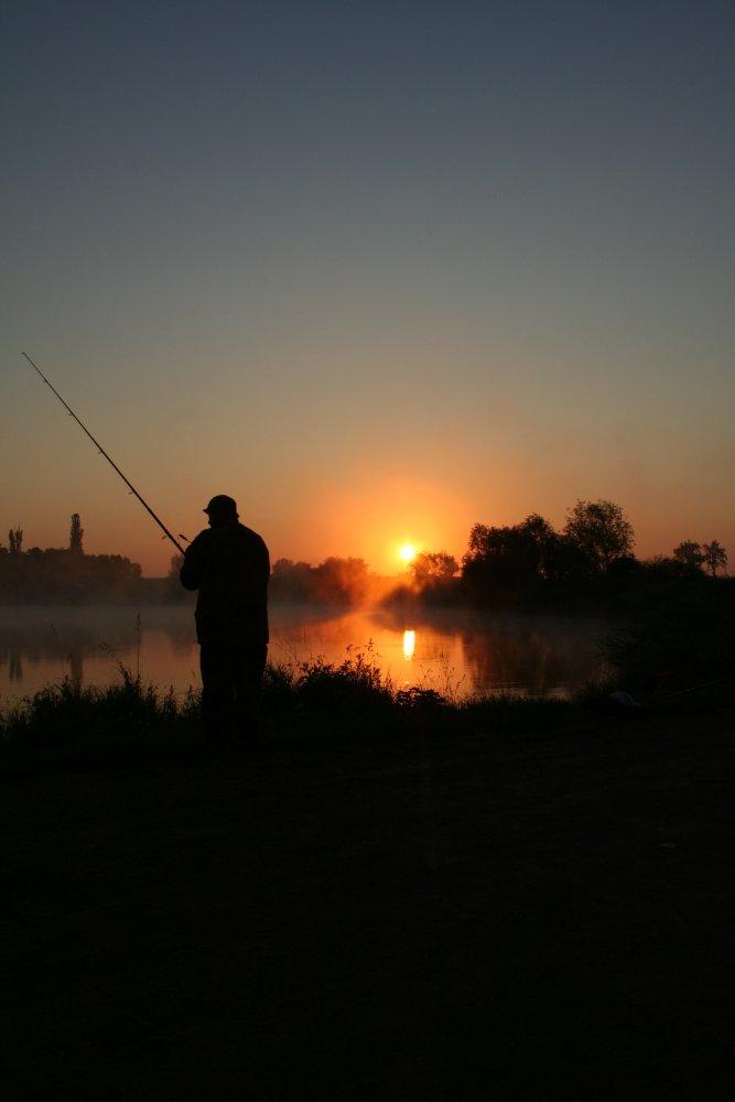 Einsamer Angler am frühen Morgen