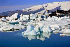 Eis bricht vom Gletscher ab und schmilzt im See langsam dahin.