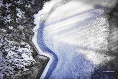 Eisiger Bach mit Eiskruste