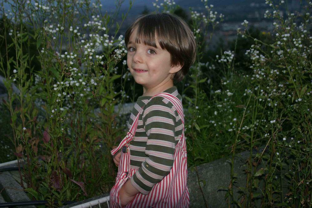 Enkel auf Terrasse mit blümerantem Hintergrund
