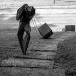 Escultura de bronce.El ser humano con su carga.