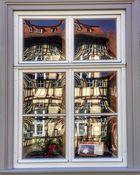 Fachwerfassade spiegelt im Butzenfenster