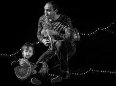 Father and son playing darbuka