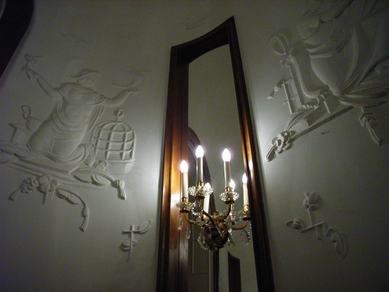 Figürliches Relief mit Spiegel und Armleuchter