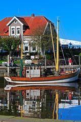 Fischerhaus und Kutter im Hafen von Neuharlingersiel