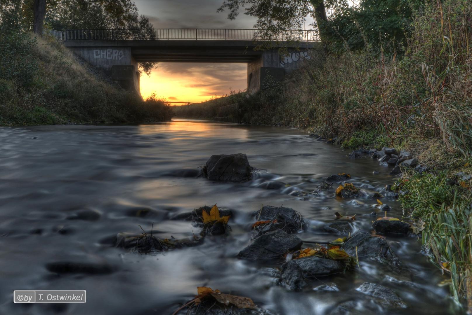 Fließendes Gewässer bei Sonnenaufgang