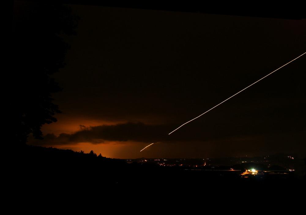 Flugzeugspur in einer Gewitternacht