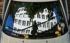Fotograf auf Treppe mit Fassade im Rücken Blätter auf einem Auto fotografierend und sich spiegelnd