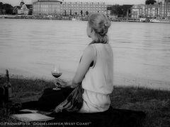 Frau sitzt am Rhein