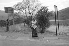 Frau wartet an der Straße (Südafrika)