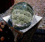 Glaskugel auf einem Steinbrunnen vom Wasser getragen und bewegt