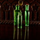 green bottles  on mahogany table