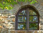 Herbstlaub im Fensterspiegel