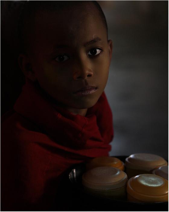 Im Dunkel des Tempels stand dieser junge Mönch und wartete auf Spenden