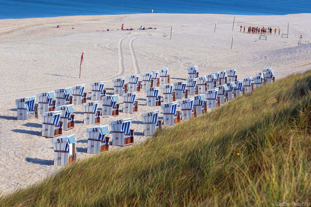 In einer Reihe Strandkörbe mit Beachvolleyballplatz