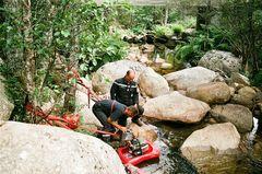 Installation d'une motopompe dans une rivière pour le ravitaillement des camions.