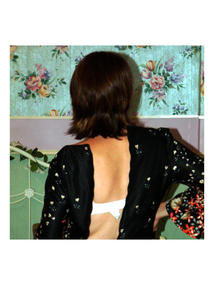 J.S. und ihr wunderbarer Rücken mit Schild beim Einkleiden vor einer Tapete