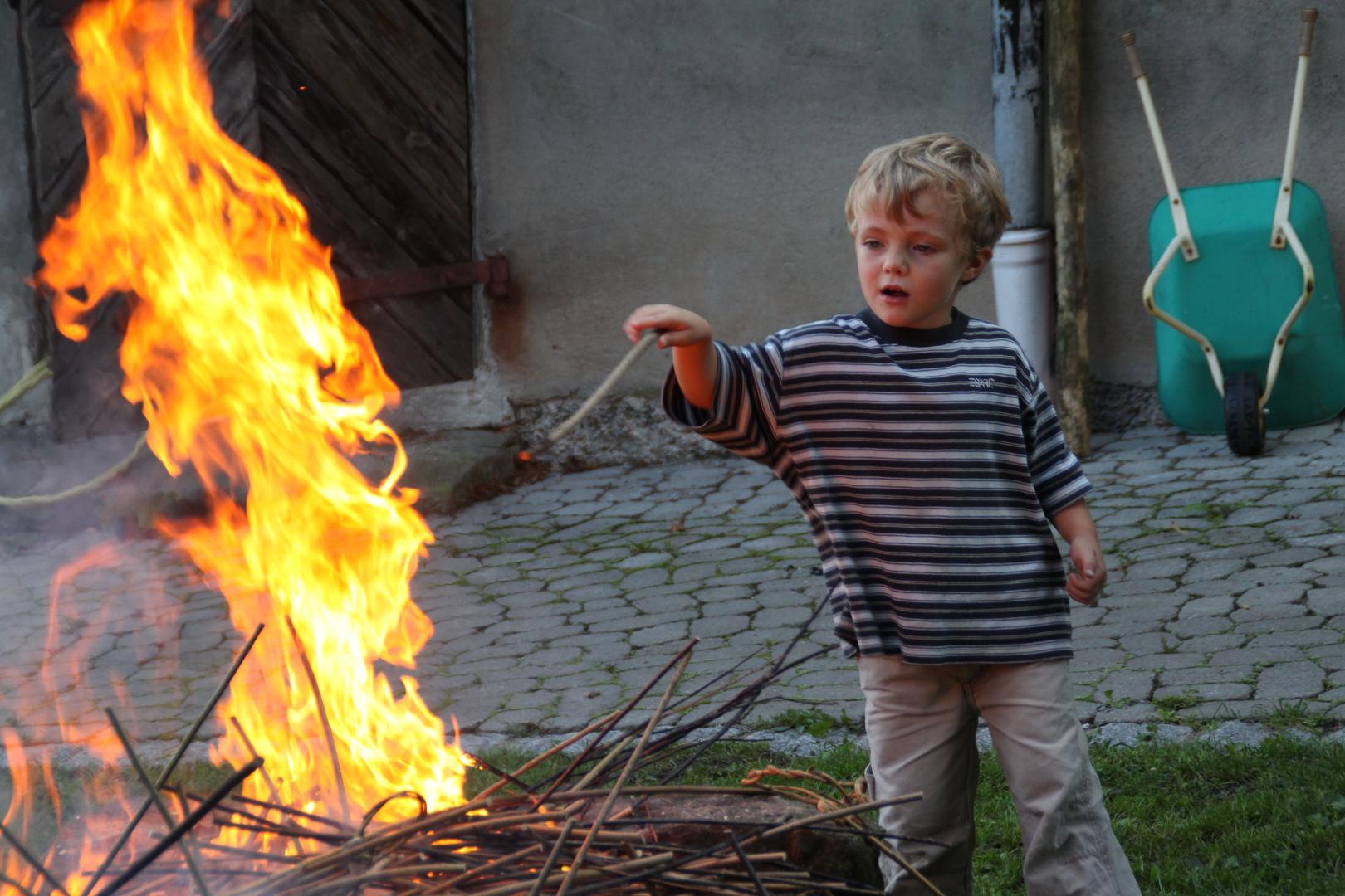 Junge am Feuer