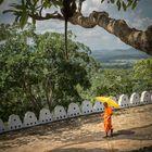 Junger Mönch mit Regenschirm