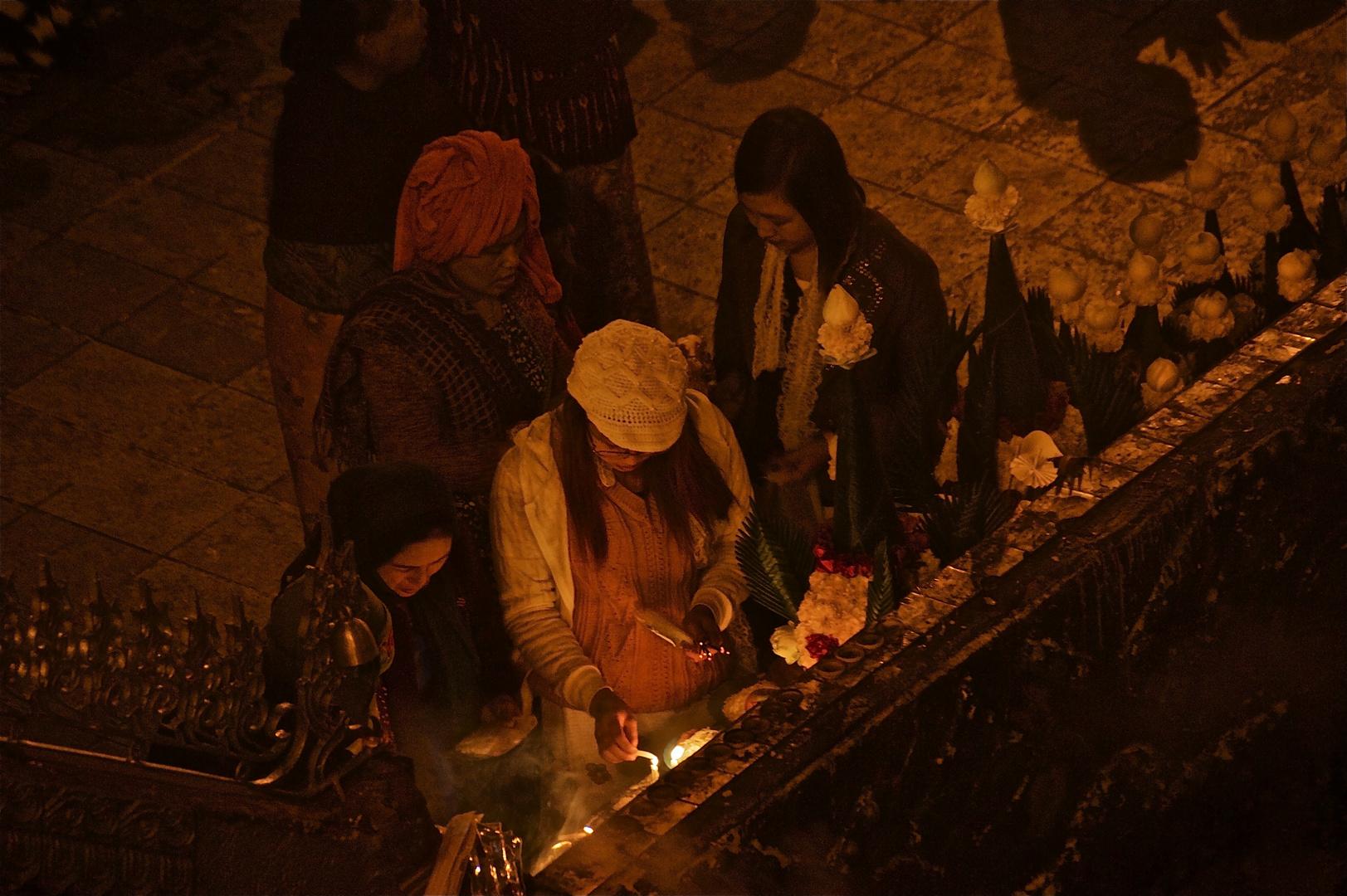 kerzen für buddha neben betenden schatten
