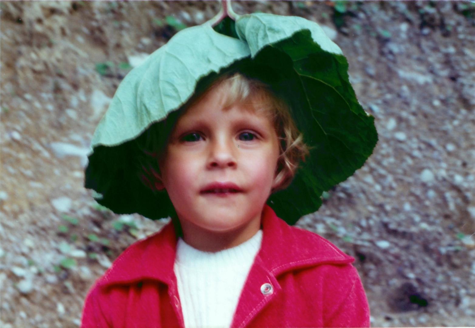 Kind mit einem Blatt auf dem Kopf