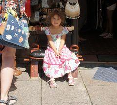 Kleines Mädchen auf einem Bänkchen vor einem Laden