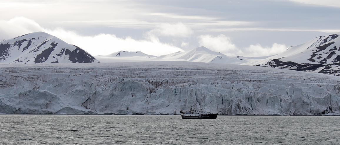 kleines Schiff vor großem Gletscher