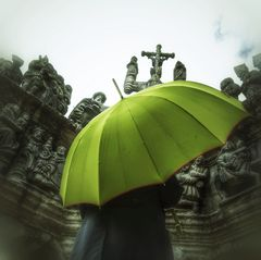La femme au parapluie arrive à l'enclos paroissial de Guimiliau (74)