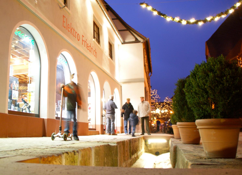 Ladenburg und der beleuchtete Kandelbach am Abend.