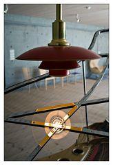 - Lampe mit Spiegelung vor Beton über Poul Henningsen Piano -