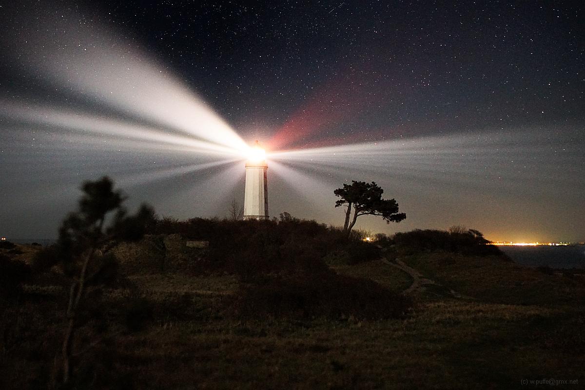 Landschaft mit Leuchtturm bei Nacht