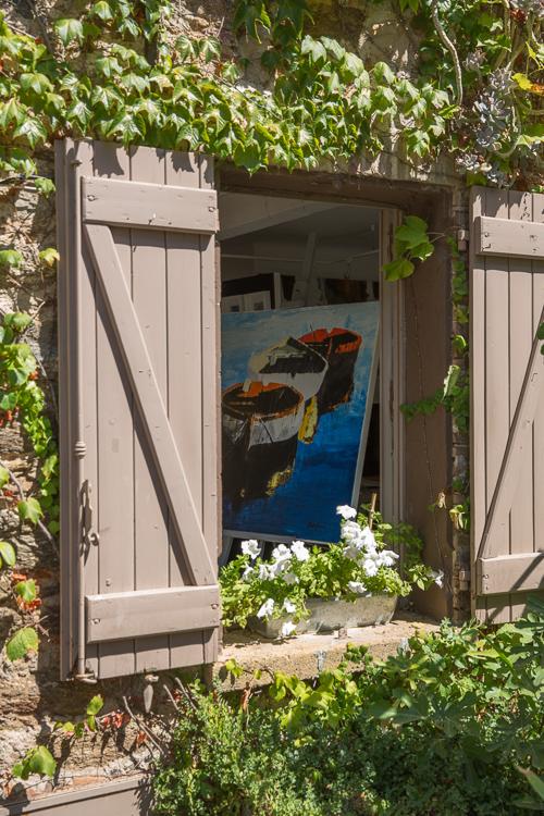 L´artiste et ses oeuvres dans la fenêtre