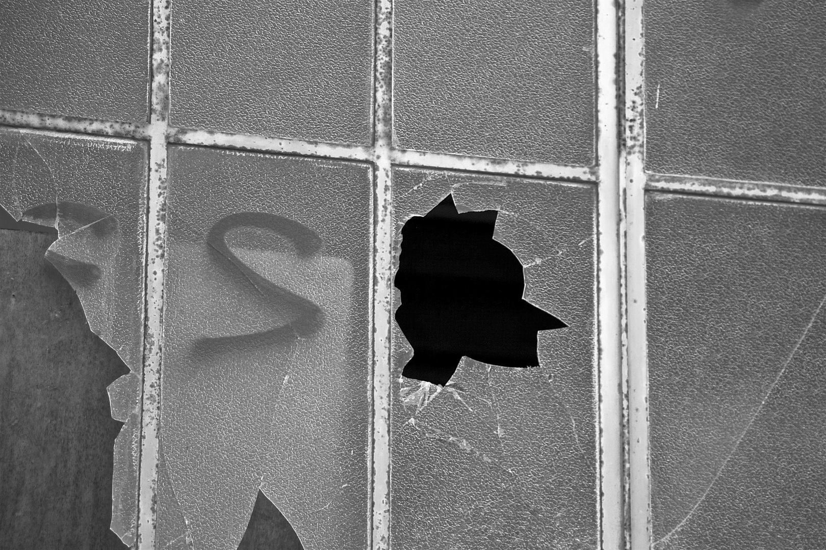 Le visage sur la vitre vandalisée.